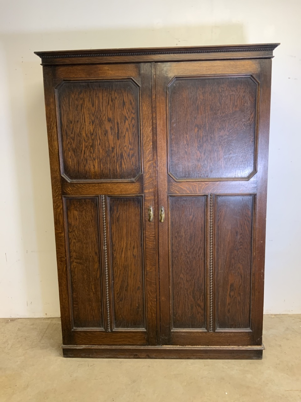 An early 20th century gentleman's oak double wardrobe by Awlyn furniture with fitted shelves,