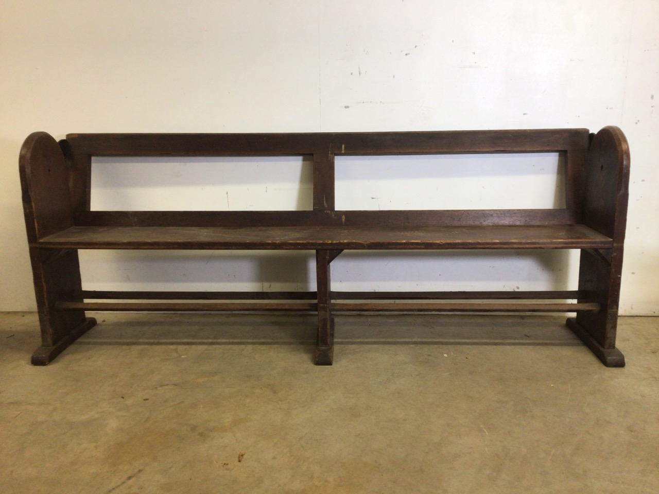 A pitch pine pew with reversable back rest and double footrests. W:215cm x D:50cm x H:82cm