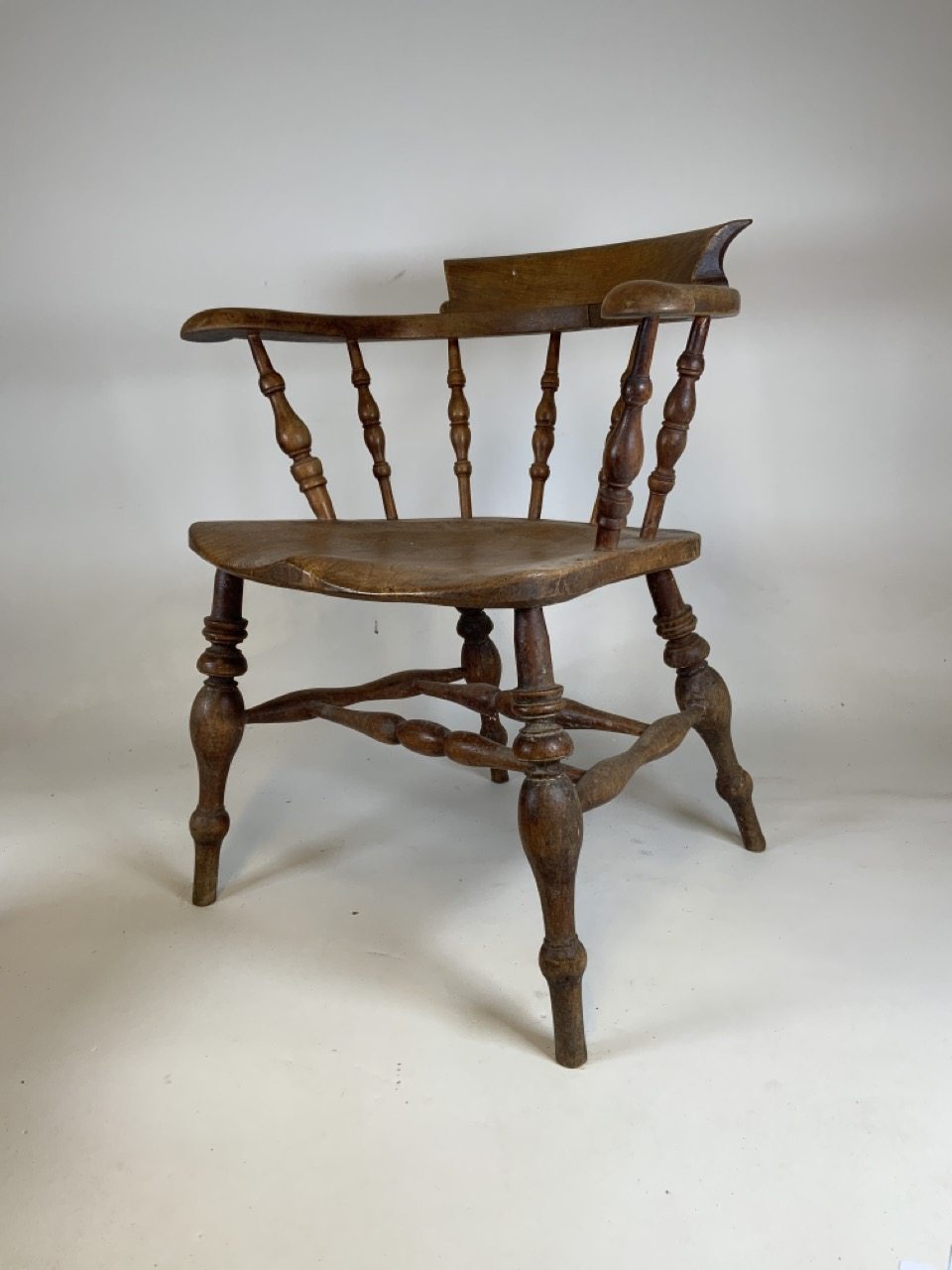 A Victorian smokers bow arm chair with curved top rail and turned spindles with saddle shaped seat