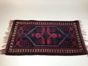 A Turkish prayer rug, maroon and navy. W:103cm x D:57cm x