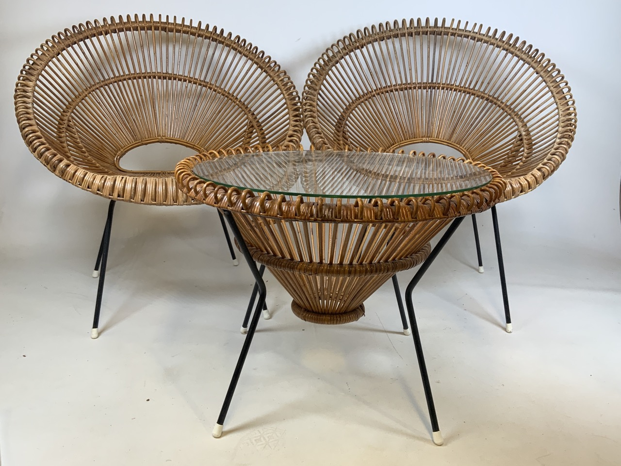 A Franco Albini mid century circular coffee table in wicker and metal with glass top and two