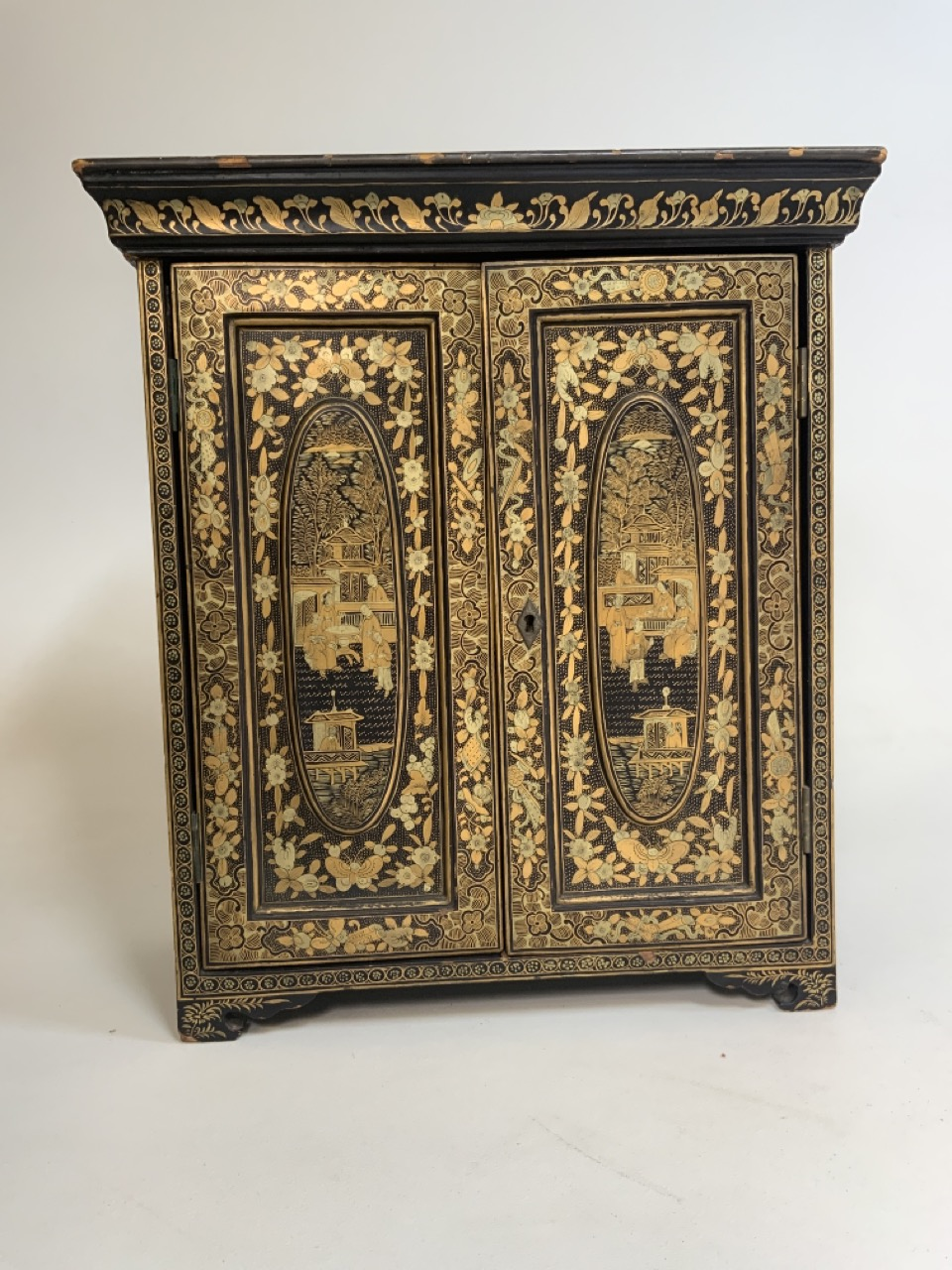 A black lacquered Japanese jewellery chest of five drawers with extensive gilt painted decoration
