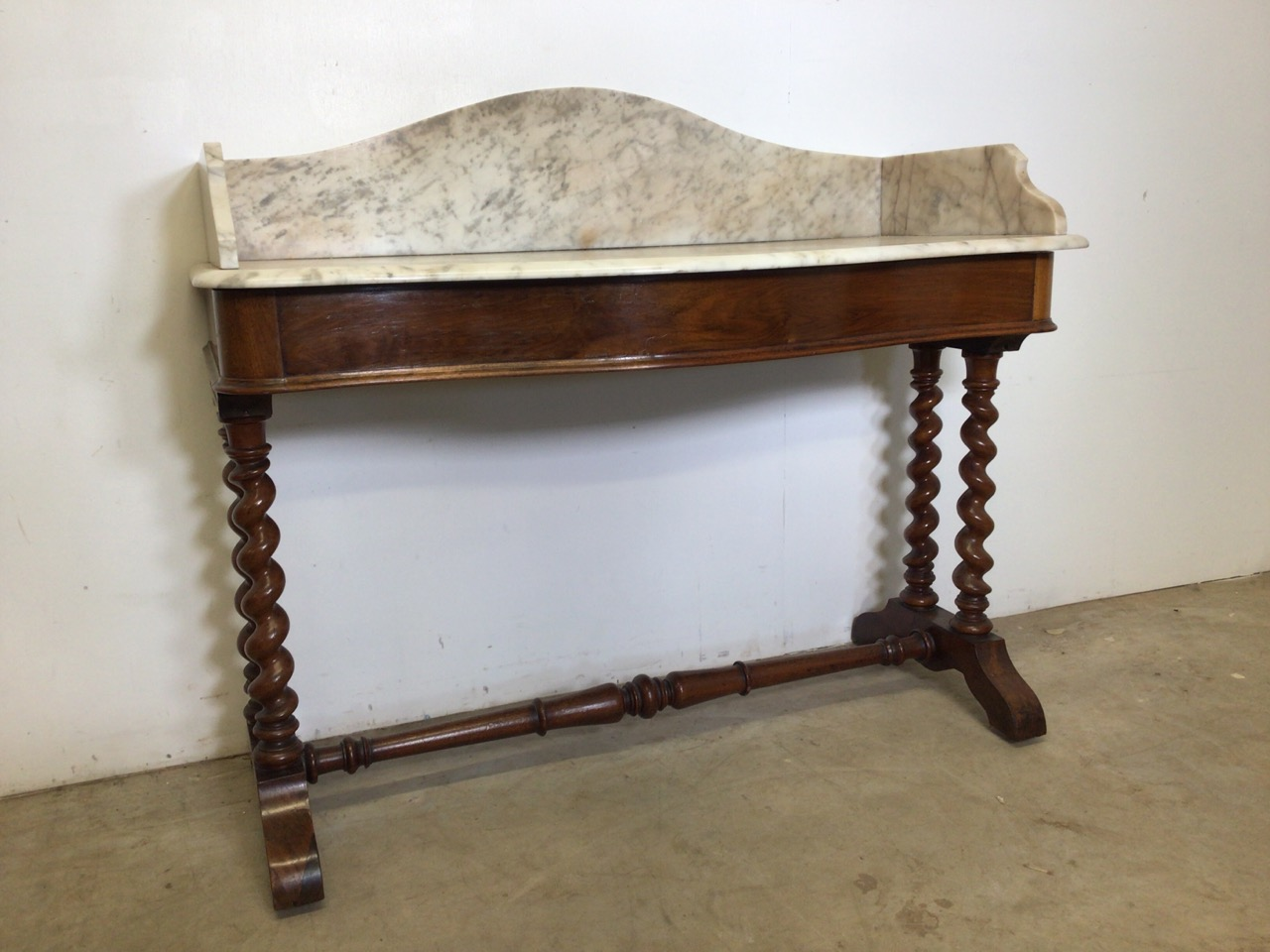 A serpentine front mahogany marble topped wash stand with large barley twist legs and turned