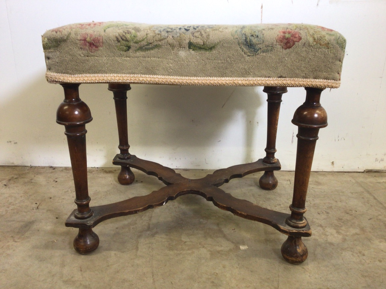A Victorian mahogany upholstered stool with turned legs and X frame stretcher bar to base. With