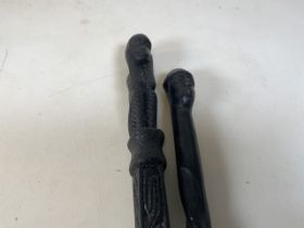 Two carved walking sticks - one with a carved monkey pommel and the other with a carved head .
