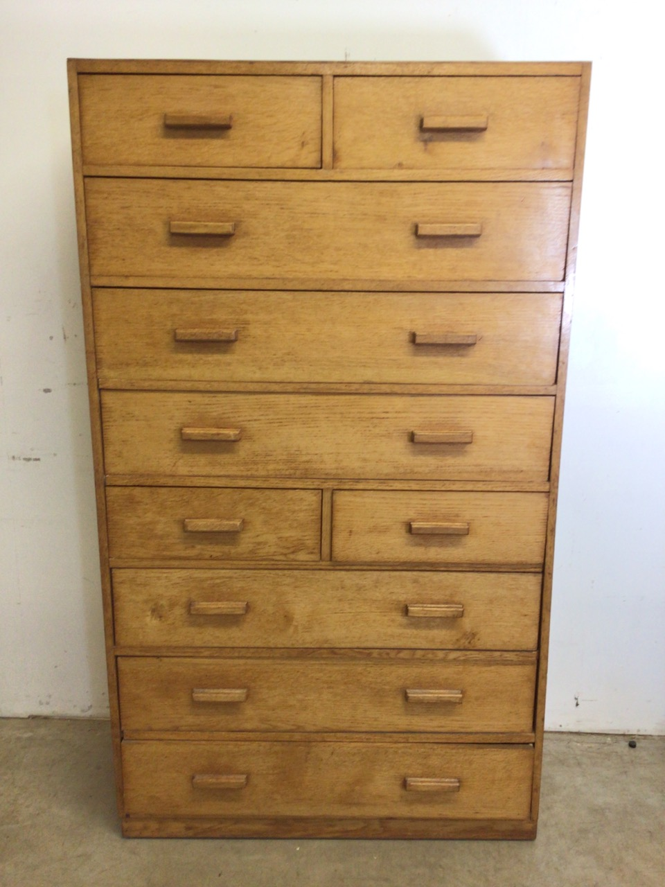A mid century oak fronted ten drawer tall boy with original handles. W:91cm x D:41cm x H:158cm