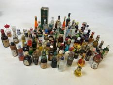 A large collection of miniatures including rum, port, whisky and tequila. A few empties for
