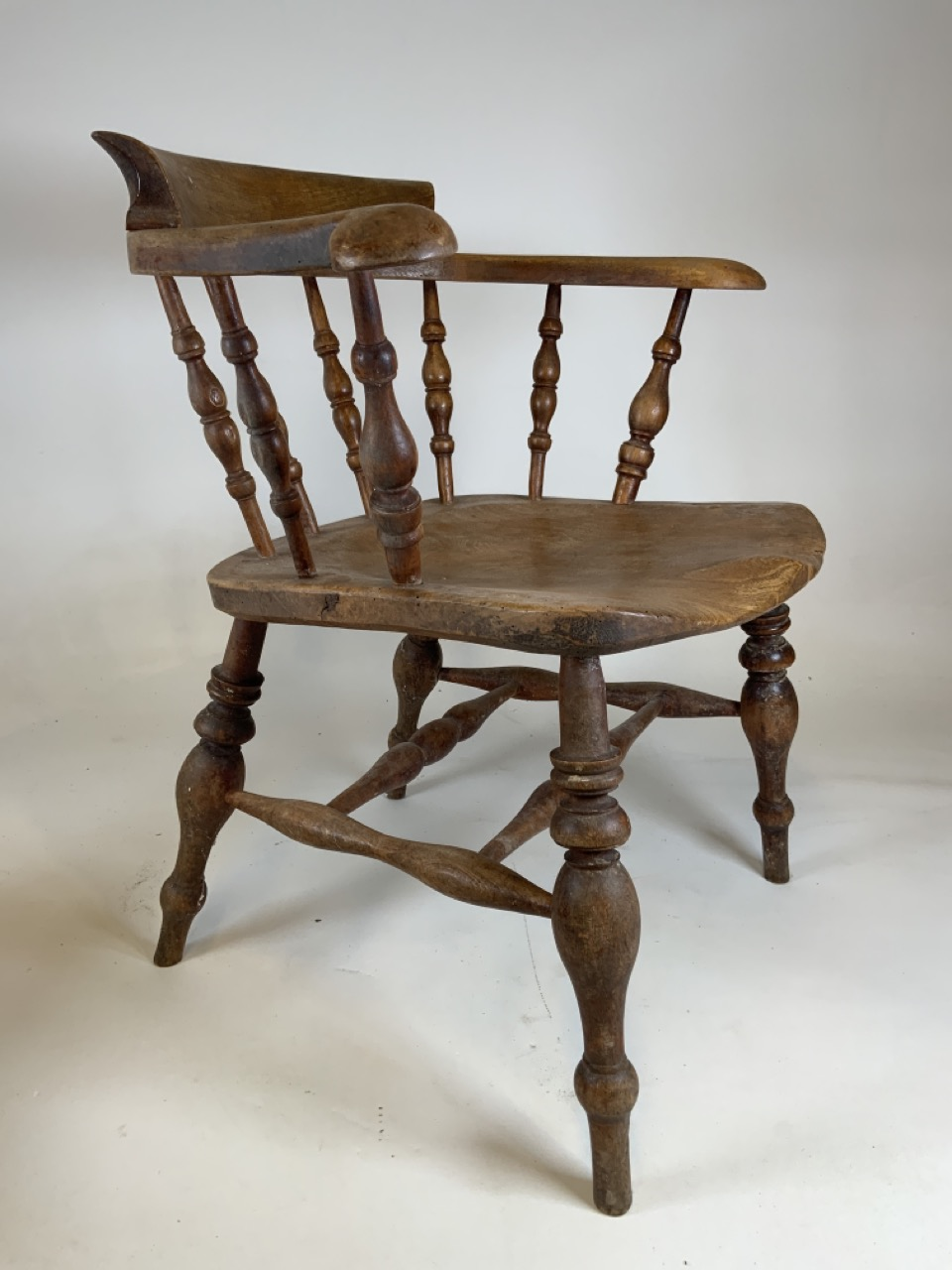 A Victorian smokers bow arm chair with curved top rail and turned spindles with saddle shaped seat - Image 7 of 10