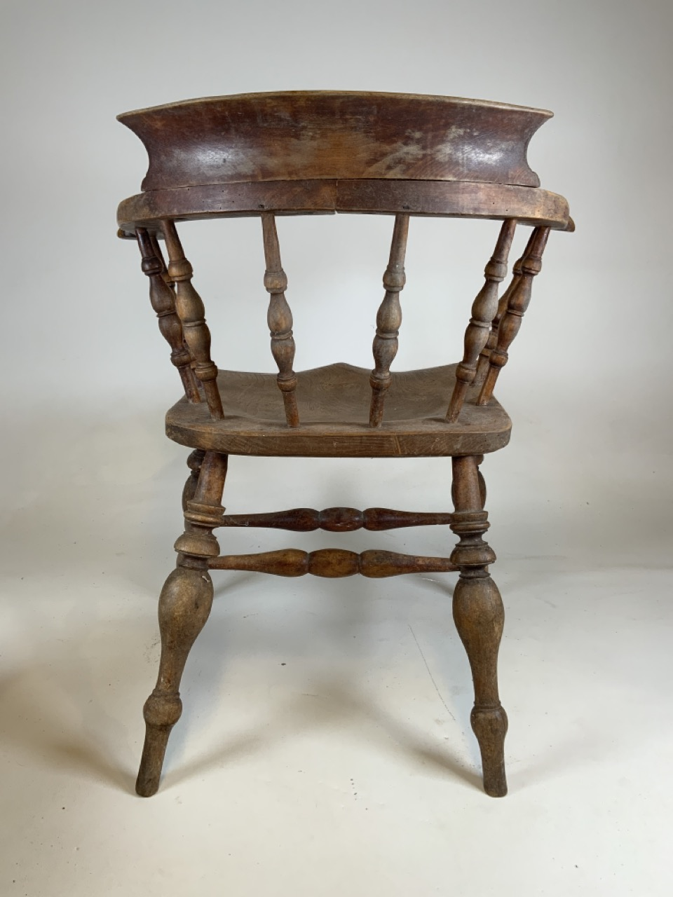 A Victorian smokers bow arm chair with curved top rail and turned spindles with saddle shaped seat - Image 8 of 10