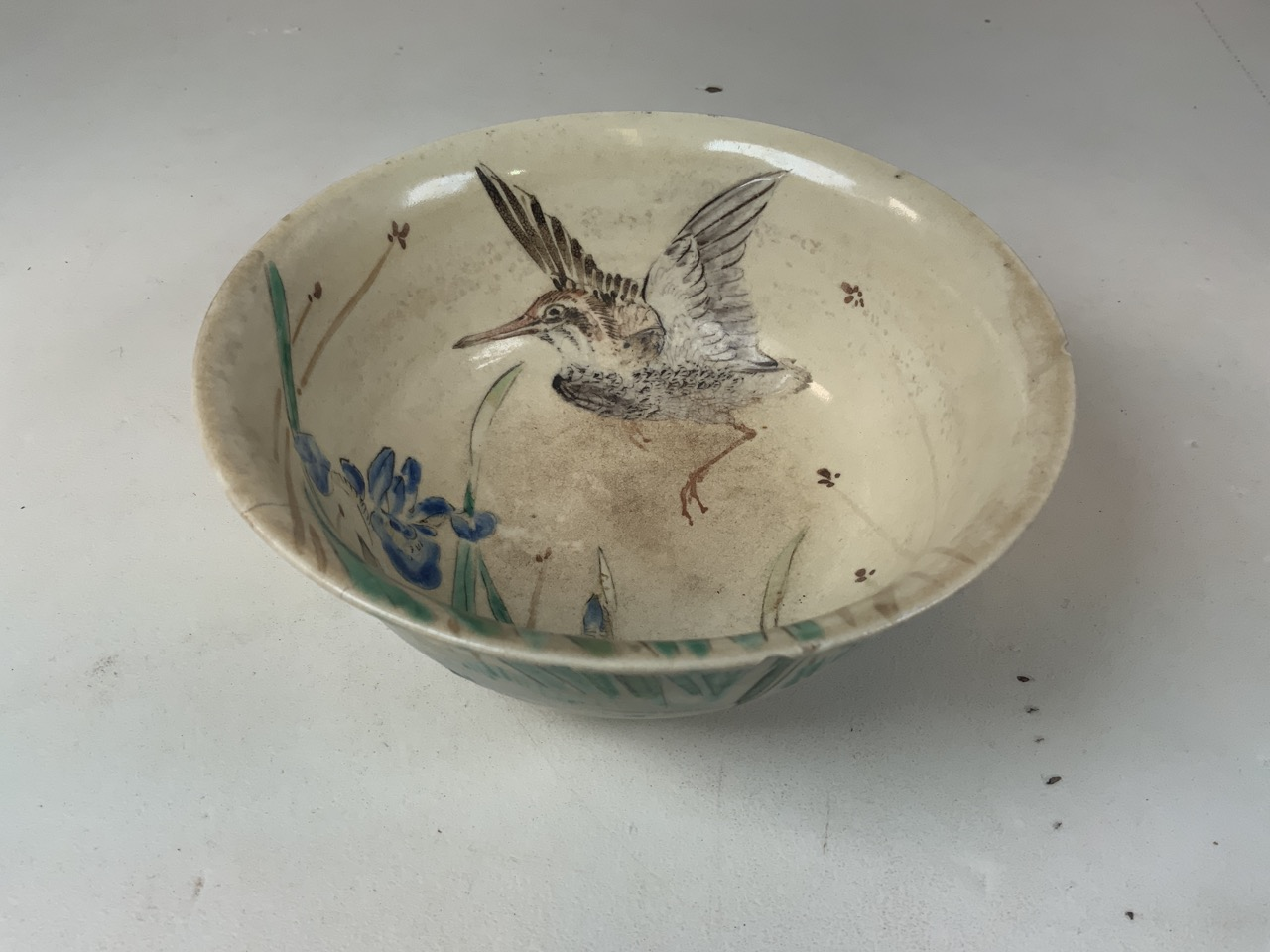 An oriental hand painted bowl with bird image to interior. Oriental markings to base. Chip to rim