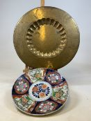 An Imari style Japanese charger (restored) 42cm together with an Eastern brass charger engraved with