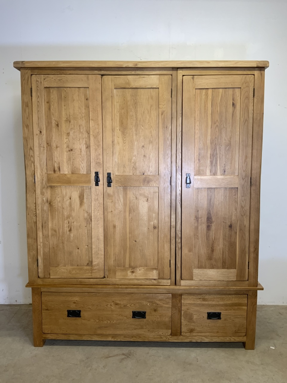 A modern oak triple wardrobe with deep drawers to base and interior hangings rail to top.