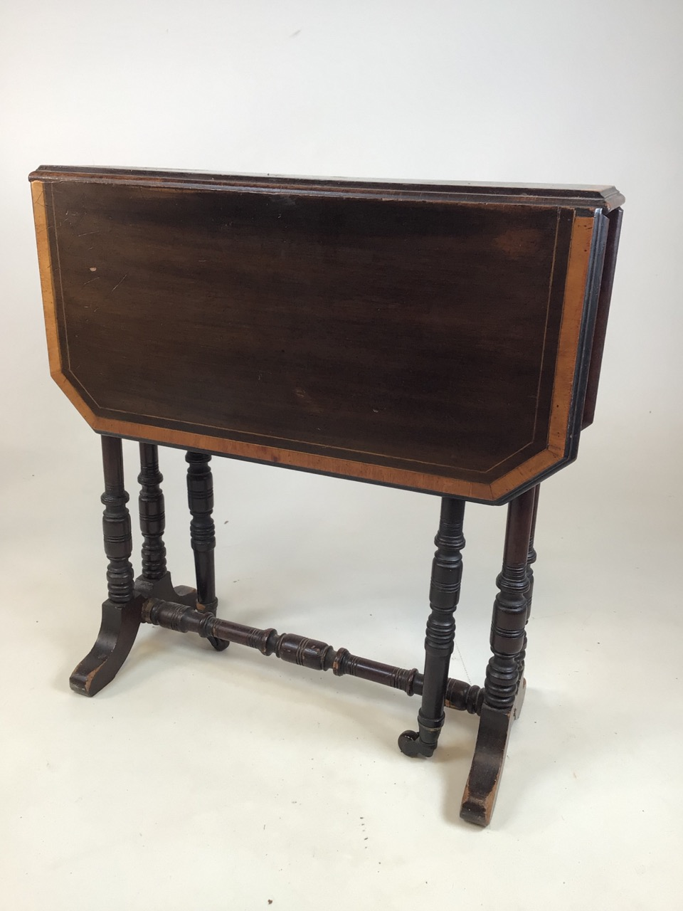 A small Edwardian mahogany inlaid Sutherland table with turned legs and stretcher with ceramic