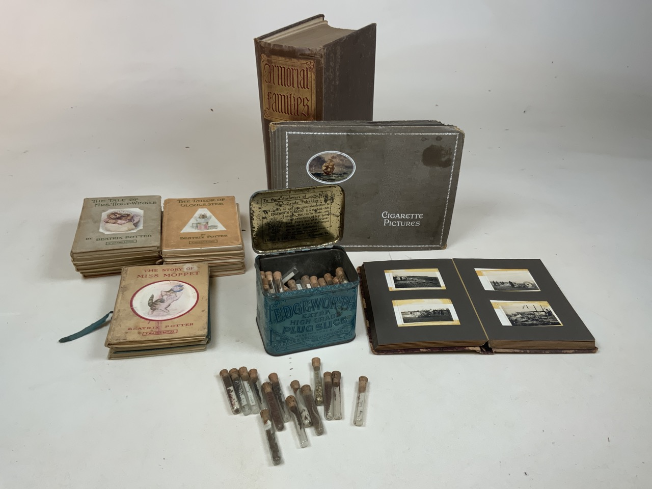 An album of cigarette cards, a collection of Beatrix Potter book A/F, a tobacco tin with glass vials