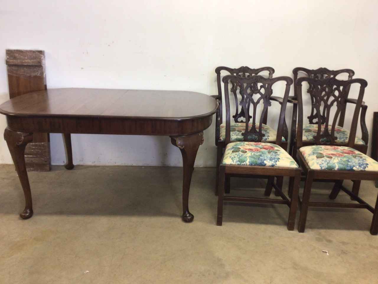 A mahogany extending table on cabriole legs with two extra leaves with four Victorian chairs to