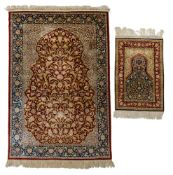 A silk Hereke rug, signed; added a ditto smaller rug, 124 x 197,5 / 61 x 88,5 cm