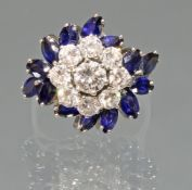 Ring, WG 585, 1 Brillant ca. 0.25 ct., 8 Brillanten zus. ca. 0.80 ct., etwa w/vsi, 14 Saphire im Na