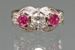 Ring, WG 750, 1 Brillant ca. 0.51 ct., etwa tw/lpr., 2 runde facettierte Rubine zus. ca. 0.40 ct.,