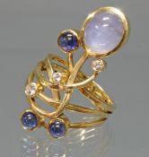 Ring, Atelier Heinemann, Köln, GG 750, 3 Brillanten zus. ca. 0.20 ct., 1 großer Stern-Saphir, 3 S