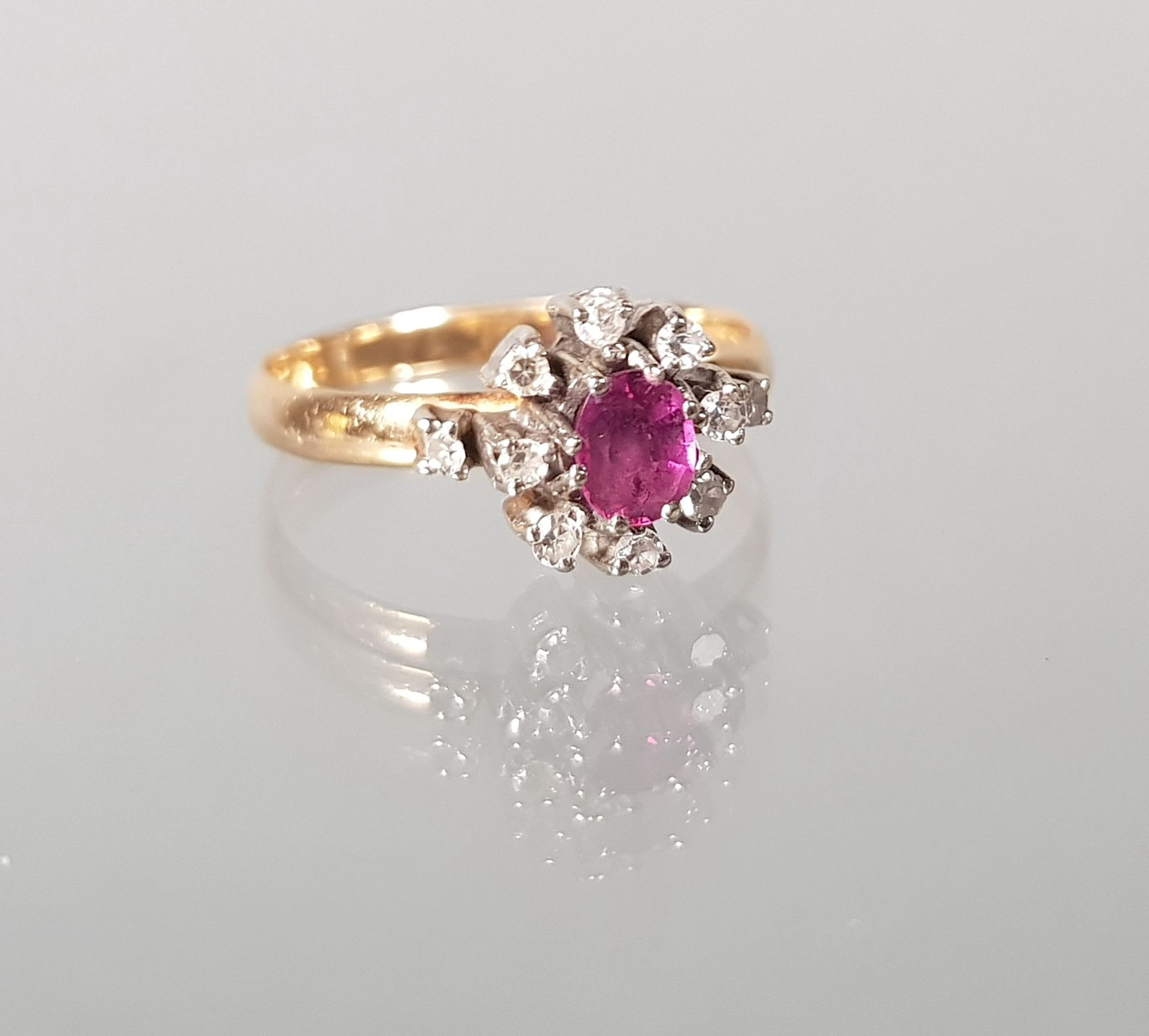 Ring, GG 750, 1 ovaler facettierter Rubin, 10 kleine Besatz-Diamanten, 3 g, RM 18