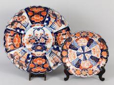 Großer und kleinerer Teller mit Imari-Dekoren; Japan; 19. Jh.<br><br>Porzellan mit unter Glasur koba