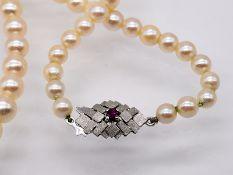 Akoja-Perlenkette mit weißgoldener Schließe und kleinem Rubin; 90- er Jahre.<br><br>Akoja-Perlen; im