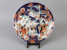 Großer Teller mit figürlichem Imari-Dekor; Japan; um 1900.<br><br>Porzellan mit unter Glasur kobaltb