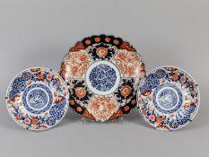 3 Teller mit Imari-Dekor; Japan/China; Anfang 20. Jh.<br><br>Porzellan mit unter Glasur kobaltblauem