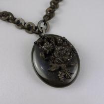 Medaillon an Ringkette, Trauerschmuck, um 1890ovales Medaillon mit plastischem Blumenbukett