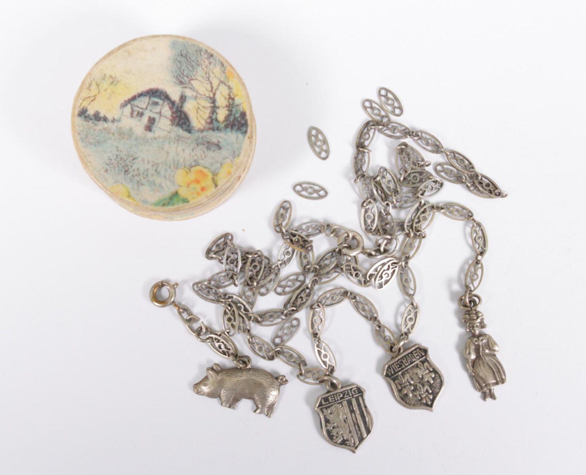 Runde Schmuckschachtel mit Bettelarmband und gerissener Halskette aus Silber