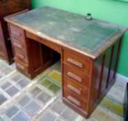 A 1930 oak pedestal desk, central arched door, four drawers to pedestals, leather writing surface,