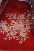 A Chinese woollen rug, with flowers, red ground, 370cm x 270mcm