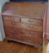 A George III oak bureau, the fall front above two short and three long graduated drawers, the