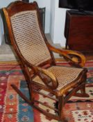 An early 20th century rocking chair, bergere back and seta, scroll arms, c.1870
