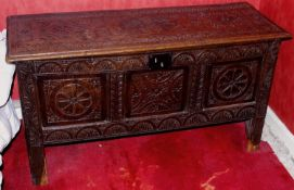 An 18th century oak blanket box, the front and top carved with floral panels and lunettes, tall feet
