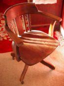 A 20th century oak swivel desk chair, four scroll legs, c.1920