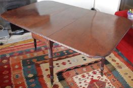 A 19th century mahogany drop leaf table, turned legs, brass casters, 143cm long, 91cm wide, c.1850