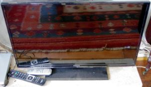 A Hitachi flat screen television and remote control, 32in