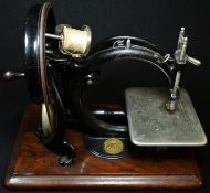 A 19th century American C-frame sewing machine, by Willcox & Gibbs, New York, wooden base, 33cm