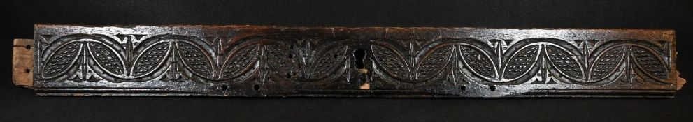 A 17th century oak fragment, carved with a band of leafy lunettes, 88cm long, c.1680