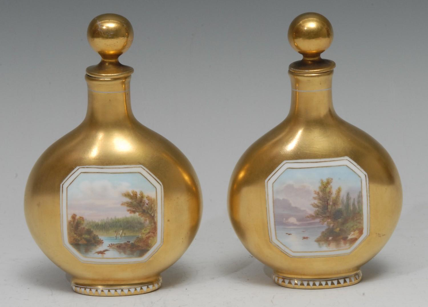 A pair of Coalport pilgrim flask scent bottles, each painted with a canted rectangular landscape