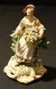 A rare Derby Patch Mark figure, Allegorical of Spring, seated holding a basket of flowers, before