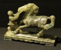 A Chinese jade coloured hardstone carving of a horse and figure, 19cm long