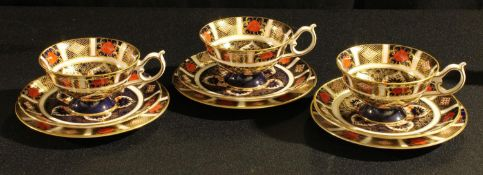 A set of three Royal Crown Derby 1128 pattern cups, saucers and side plates, first quality