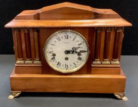An early 20th century wooden mantel clock, architectural pediment, the face with Roman numerals
