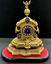 A gilt metal mantel clock under a glass dome, eagle and globe finial, blue enamelled face,