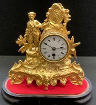 A gilt metal figural mantel clock under a glass dome, man with tricorn hat stands to one side,