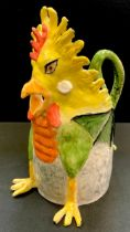 A Prue Piper (b.1938) novelty jug in the form of a ferocious cockerel a winged dragons body the tail