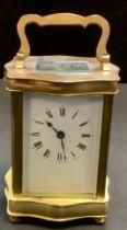 A brass carriage clock, serpentine brass body, Roman numerals. 16cm high.
