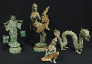 A green patinated bronze figure of a water carrier; a similar bronze dragon; two other Indonesian